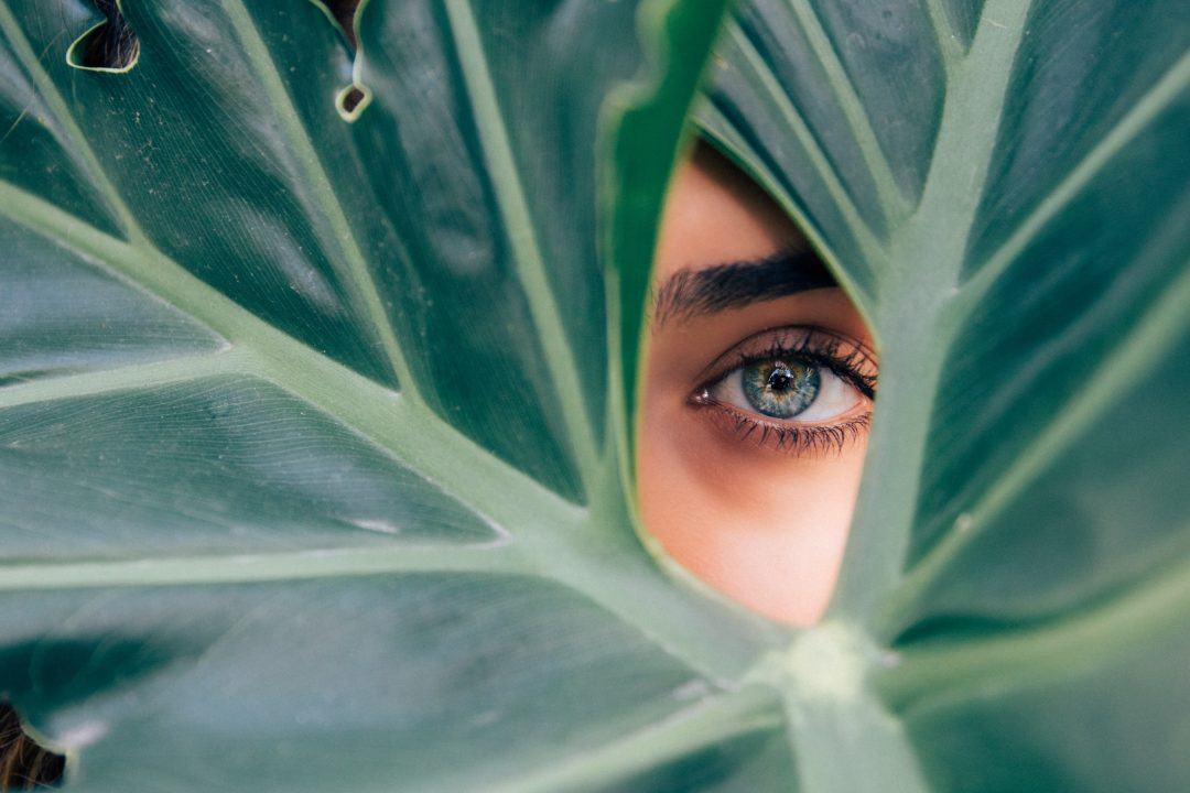 Lady looking through leaves - Sustainable Vibes
